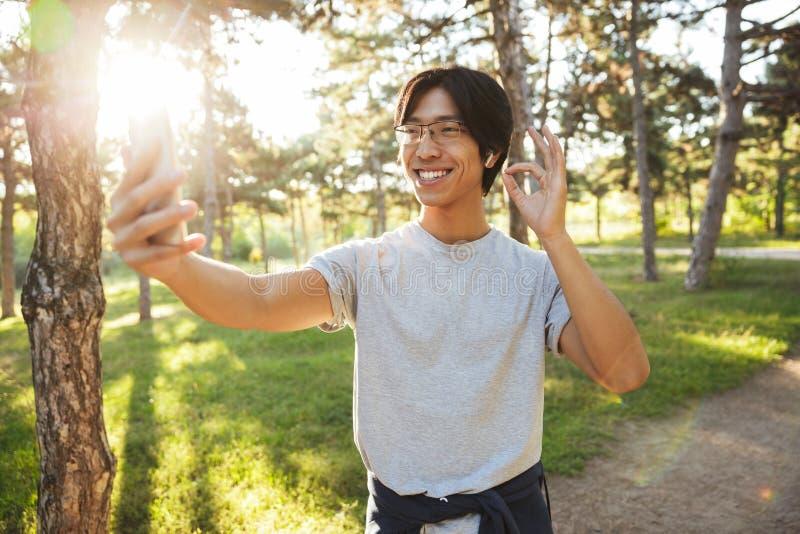 L?chelnde tragende Sportkleidung des asiatischen Athletenmannes stockfoto