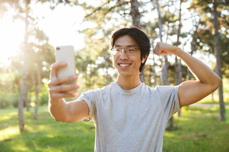 L?chelnde tragende Sportkleidung des asiatischen Athletenmannes, die ein selfie nimmt lizenzfreies stockbild