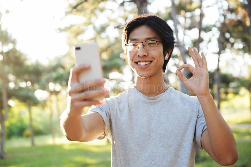 L?chelnde tragende Sportkleidung des asiatischen Athletenmannes, die ein selfie nimmt stockfotografie