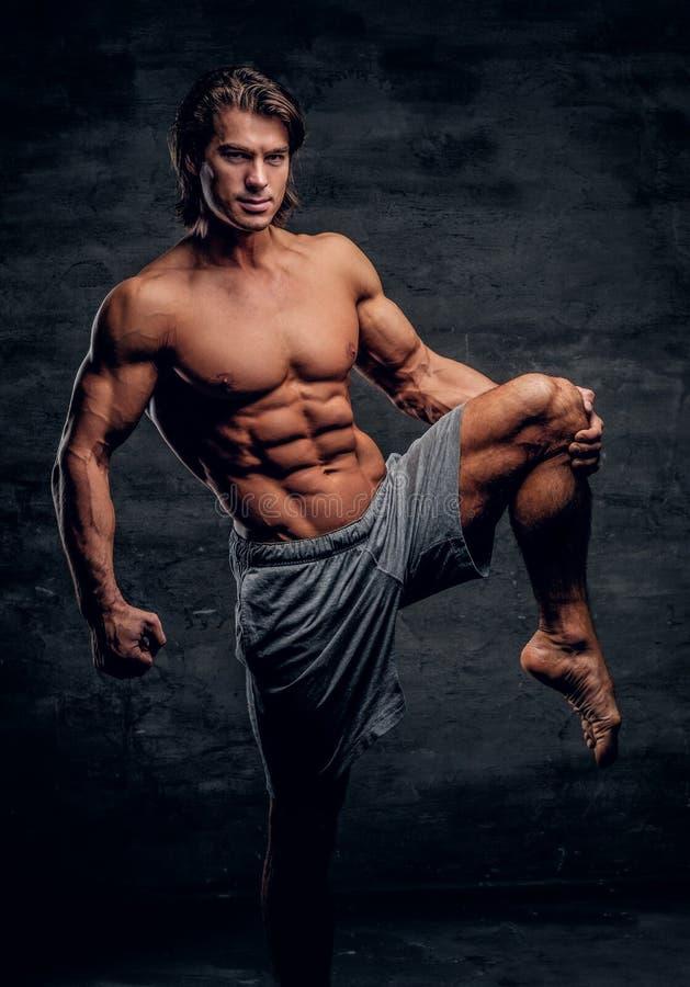 L?chelnder attraktiver Bodybuilder mit dem nackten Torso tut das strechening Bein lizenzfreies stockbild