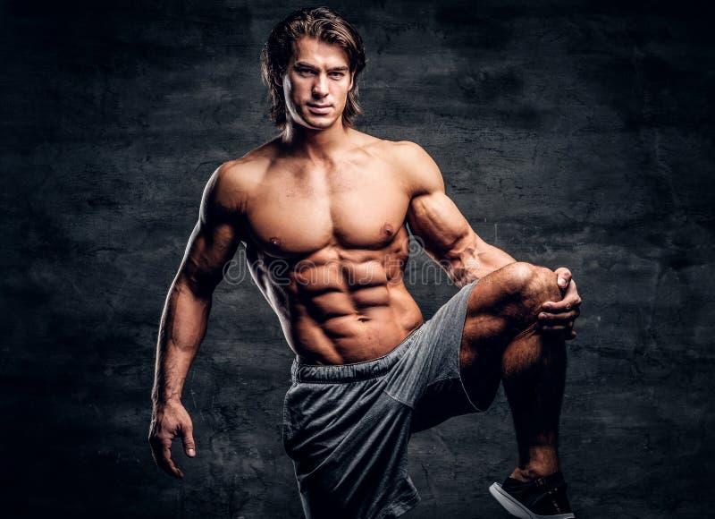 L?chelnder attraktiver Bodybuilder mit dem nackten Torso tut das strechening Bein stockbild
