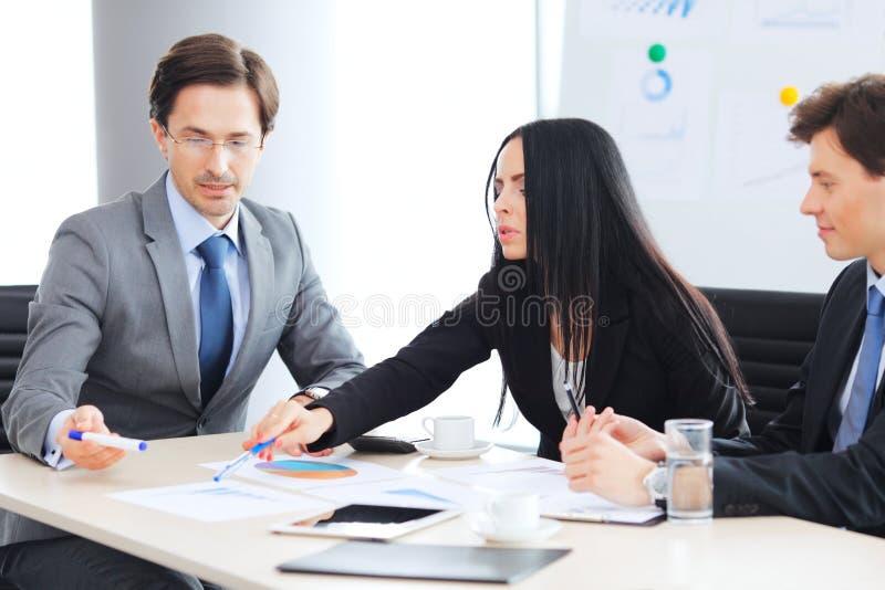 L?chelnder Gesch?ftsmann unter Verwendung des Laptop cmputer am Schreibtisch und Unterhaltung mit einer Frau lizenzfreies stockfoto