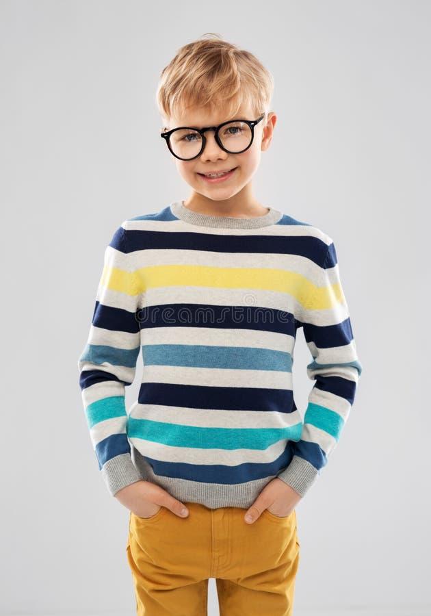 L?chelnder Junge in den Gl?sern und in gestreiftem Pullover lizenzfreies stockfoto