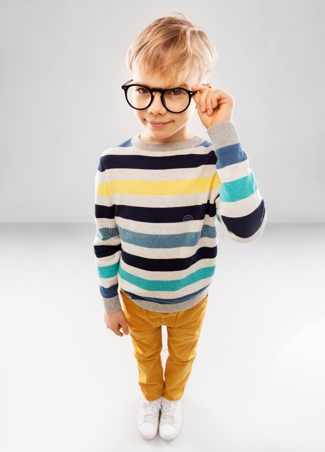 L?chelnder Junge in den Gl?sern und in gestreiftem Pullover stockfoto