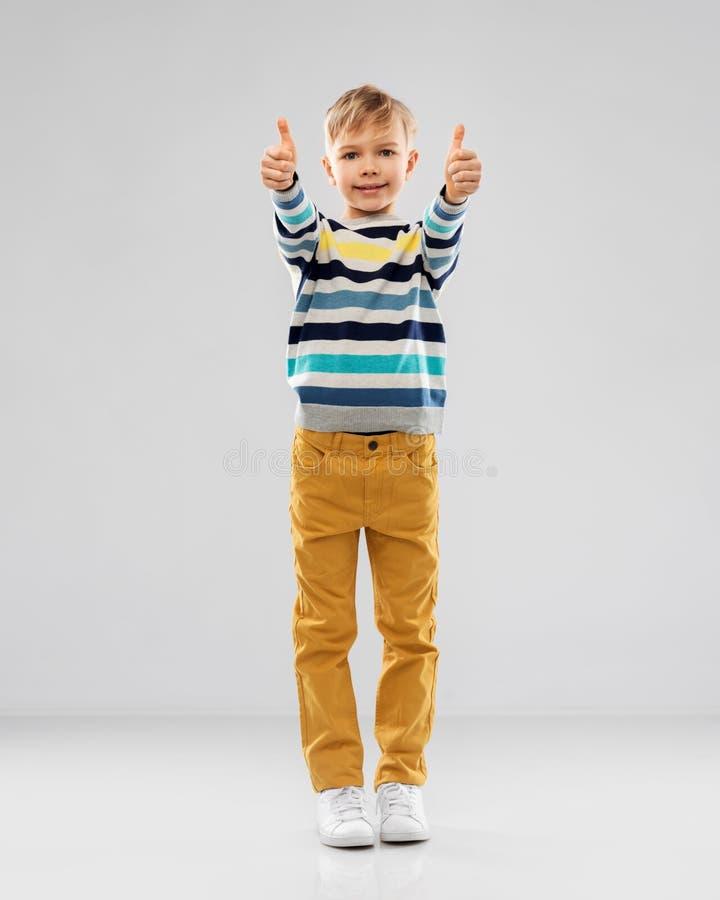 L?chelnder Junge im gestreiften Pullover, der sich Daumen zeigt lizenzfreies stockfoto