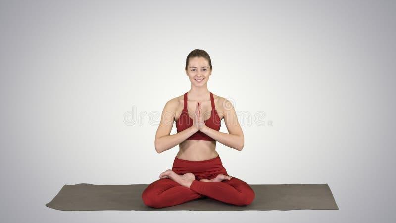 L?chelnder meditierender sitzender Lotos des Frauenyoga, H?nde verbunden auf Steigungshintergrund lizenzfreies stockbild