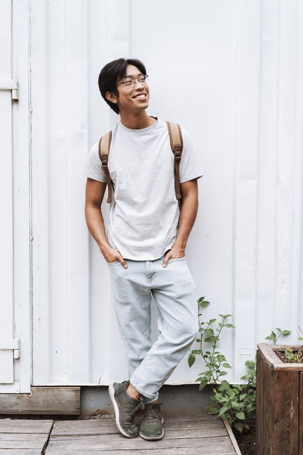 L?chelnder tragender Rucksack des jungen asiatischen Mannstudenten stockfotos