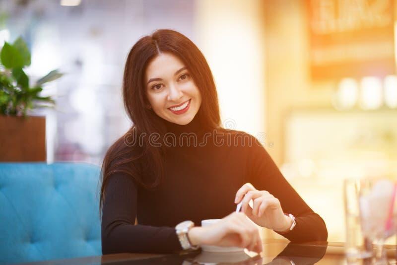 L?chelnder trinkender Kaffee der Frau im Caf? Portr?t der sch?nen gl?cklichen stilvollen Frau Mode-Lebensstil lizenzfreie stockfotos