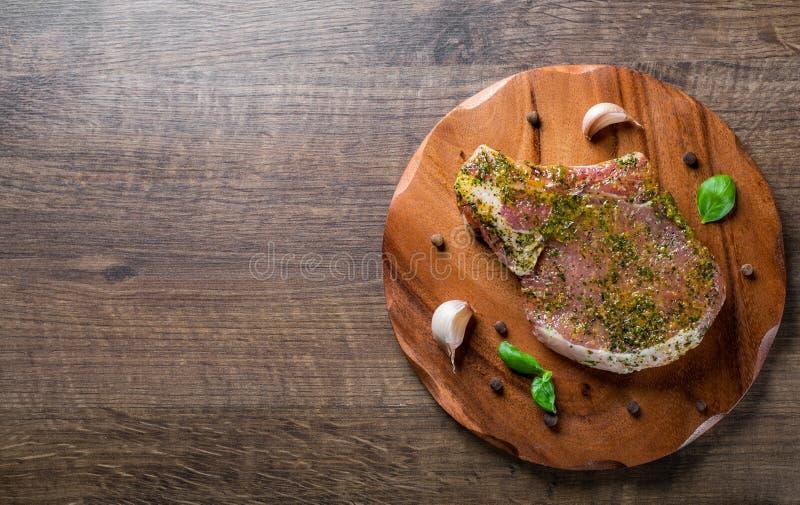 L'?chine de porc crue coupe le bifteck marin? de viande pour le BBQ sur la table en bois images libres de droits