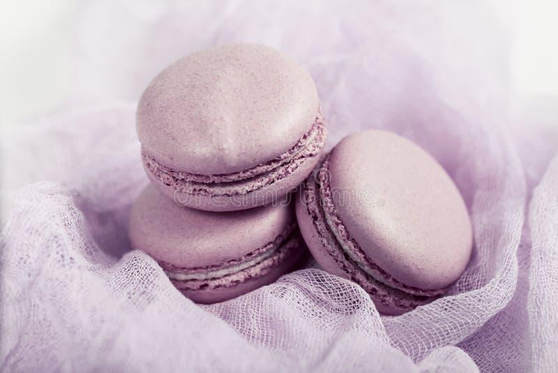 L?cker fransk efterr?tt Macaron eller makron för tre försiktig pastellfärgad mjuk rosa kakor på luftigt tyg arkivbilder