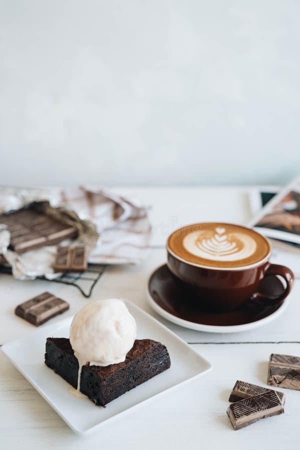 L?cker frukost p? den vita tabellen Kopp kaffe- och chokladostkakan med icecream p? vit bakgrund arkivfoton