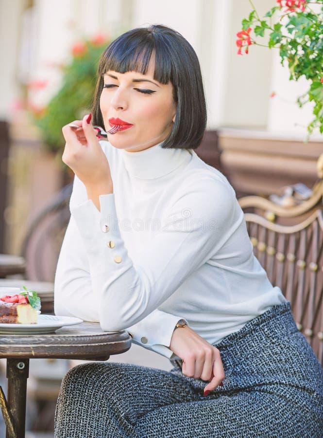 L?cker gourmet- kaka Attraktiv brunett f?r kvinna att ?ta gourmet- bakgrund f?r kakakaf?terrass Gastronomical njutning fotografering för bildbyråer