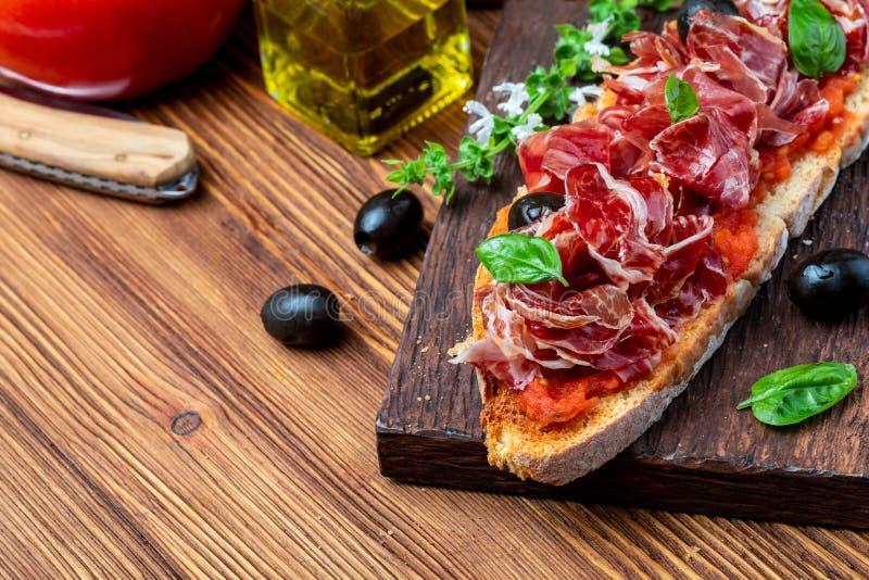 L?ckert br?drostat br?d med den naturliga tomaten, extra jungfrulig olivolja, Iberian skinka, svarta oliv och basilikasidor royaltyfria bilder