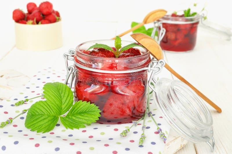 L?ckert jordgubbedriftstopp i traditionell exponeringsglaskrus p? vit tr?bakgrund arkivfoton