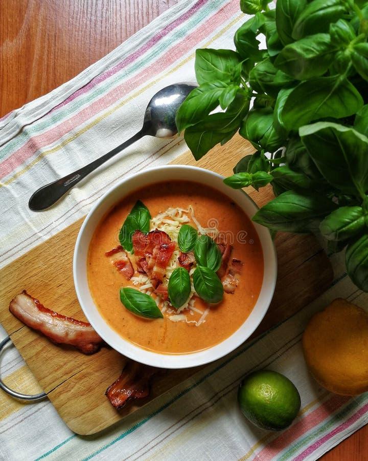 L?ckert m?l Tomatoe krämsoppa med basilika, ost, bacon och limefrukt arkivbild