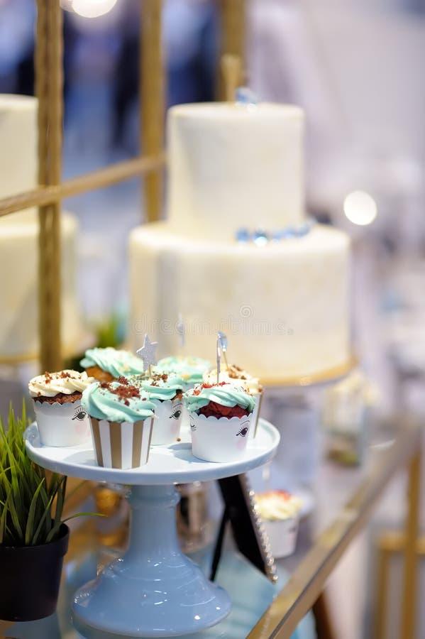 L?ckra f?rgrika gifta sig muffin med blomman och stj?rnor och h?rlig glasad kaka Stilfull s?t tabell arkivfoto