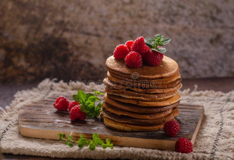 L?ckra hemlagade pannkakor med l?nnsirap royaltyfri foto