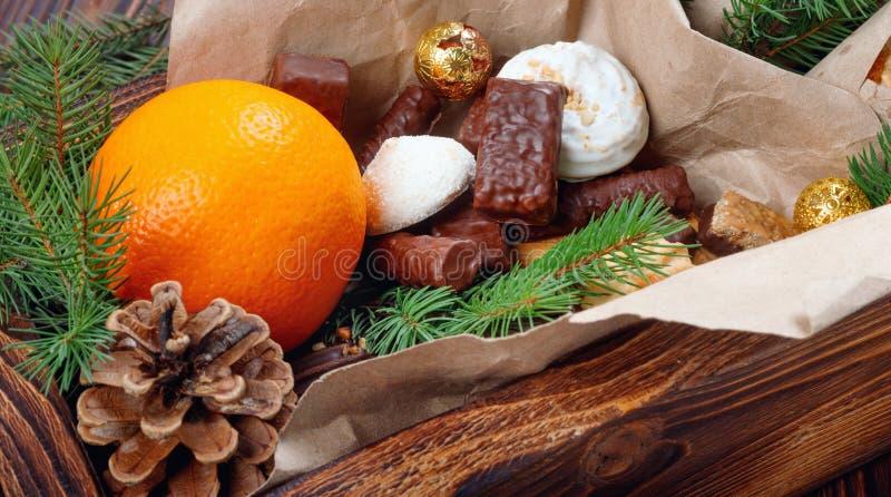 L?ckra s?tsaker, choklader, kakor och apelsiner f?r g?vor i tr?ask p? tappningtabellen royaltyfria foton
