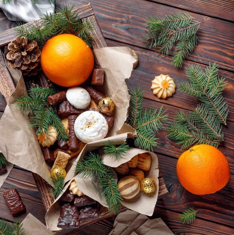 L?ckra s?tsaker, choklader, kakor och apelsiner f?r g?vor i tr?ask p? tappningtabellen royaltyfri fotografi