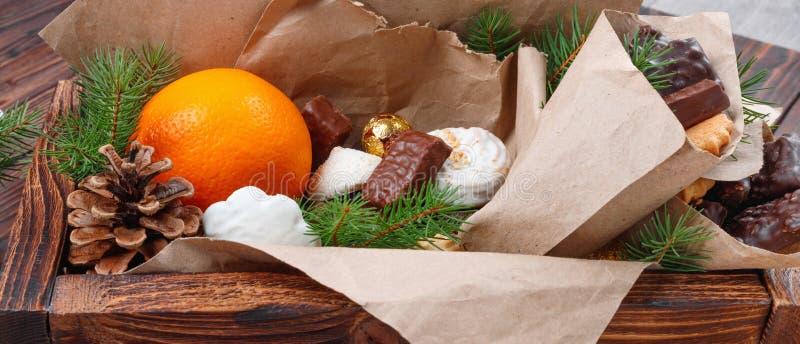 L?ckra s?tsaker, choklader, kakor och apelsiner f?r g?vor i tr?ask p? tappningtabellen fotografering för bildbyråer