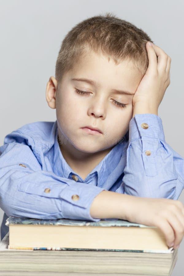 L'?colier dort sur les livres pour faire le travail Plan rapproch? Fond gris photo stock