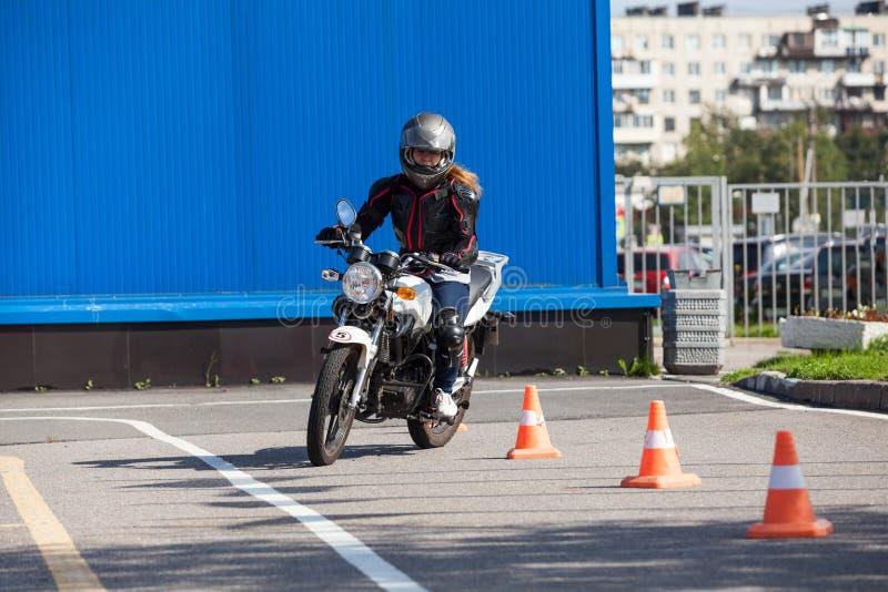 L-conducteur de femme conduisant le slalom par les cônes sur la base de formation sur la moto photos stock