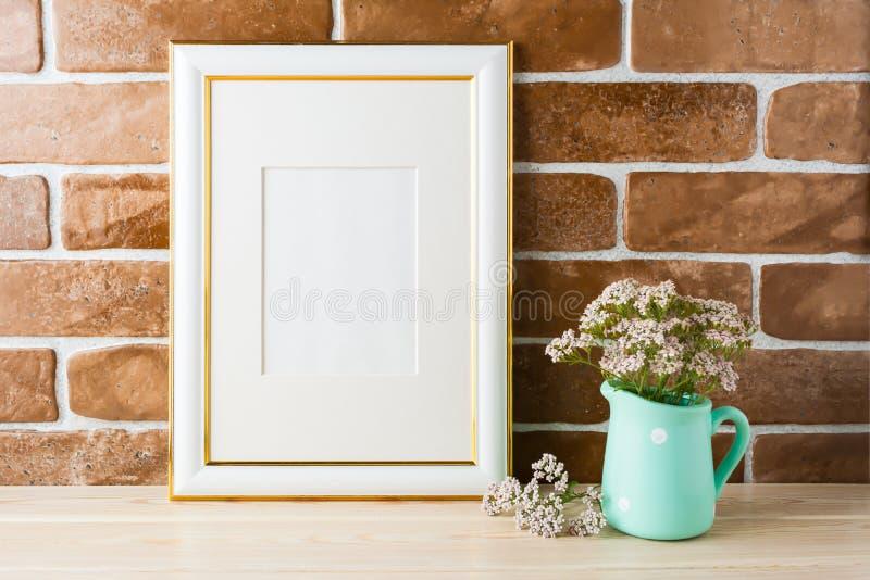 L'or a décoré le mur de briques exposé par fleurs roses molles de maquette de cadre photographie stock