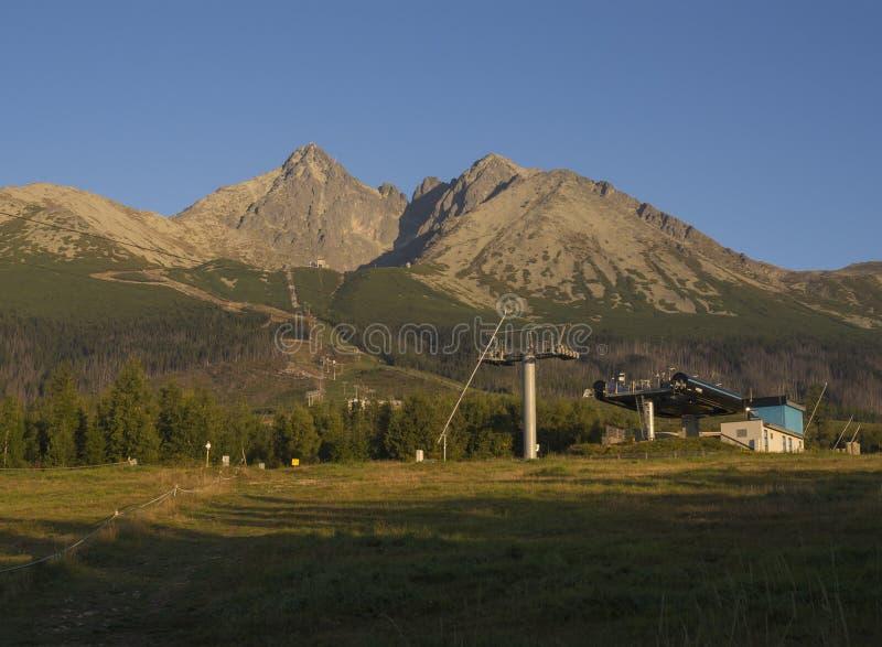 L'or de chaîne de montagnes de Tatra a coloré la lumière de lever de soleil, le remonte-pente chez Tatranska Lomnice avec les arb images stock