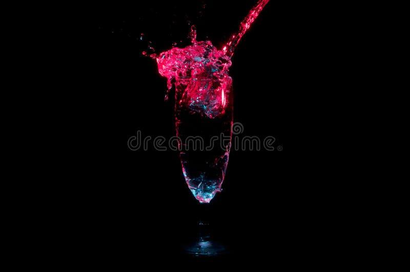 L'eau accentuée rouge éclaboussant hors du verre de champagne d'isolement sur un fond noir photographie stock libre de droits
