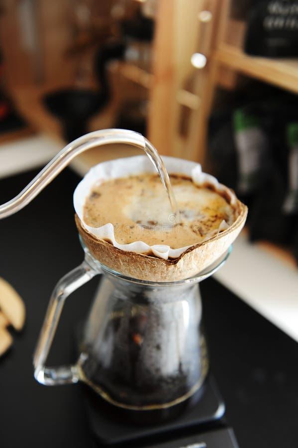 L'eau alternative d'égouttement de brassage de café de noix de coco de pourover créatif peu commun de coquille avec la bouilloire photographie stock