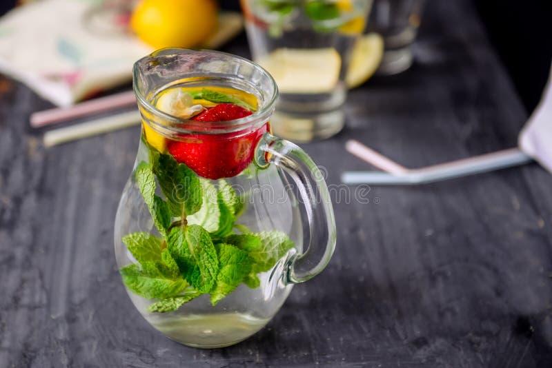 L'eau assaisonnée avec les fraises et la menthe fraîches dans des pots en verre sur une table en bois noire avec les détails lumi photos libres de droits