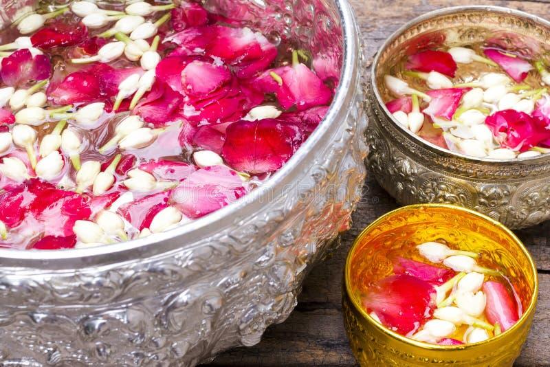L'eau avec les pétales de rose et le jasmin dans la cuvette argentée et d'or sur le vieux fond en bois pour le festival de Songkr photo libre de droits
