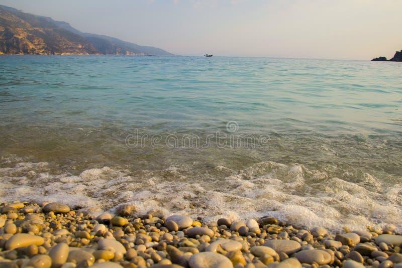 L'eau bleue avec la mousse de mer Les petites vagues viennent au rivage L'eau de turquoise avec les cailloux blancs sur la plage  image libre de droits