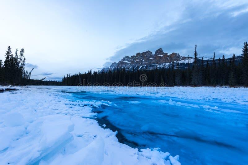 L'eau bleue de glacier circulant sur la glace en rivière d'arc à la montagne de château photographie stock libre de droits