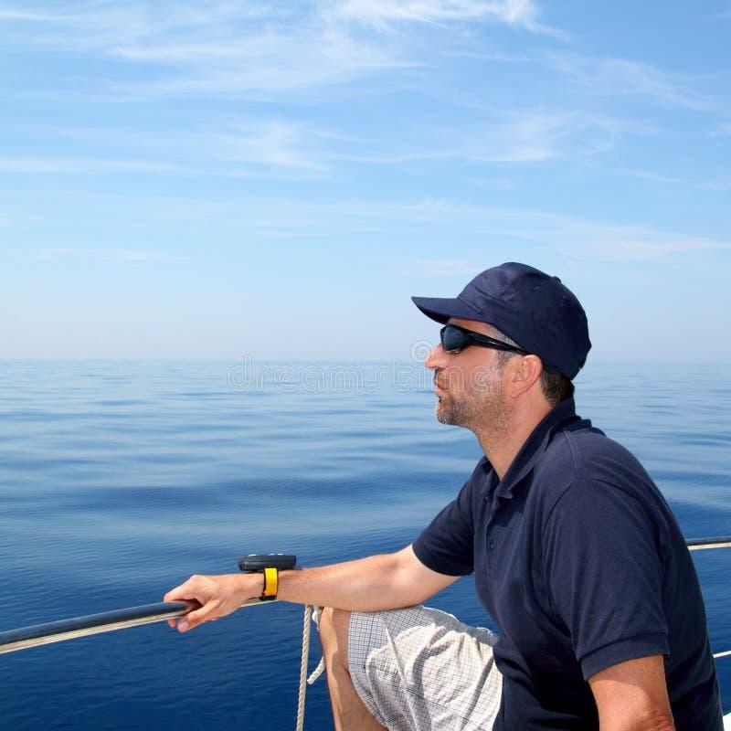 L'eau calme bleue d'océan de bateau à voile d'homme de marin photo stock