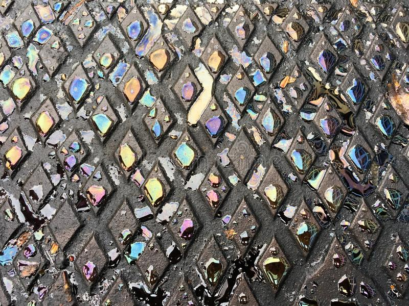 L'eau colorée se laisse tomber sur la surface métallique dans une forme de losange photo libre de droits