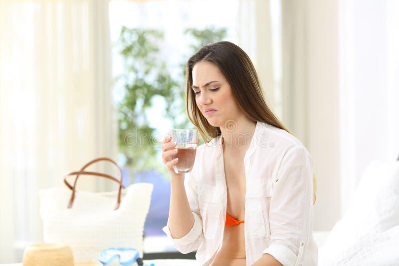 L'eau dégoûtée d'échantillon de femme avec la mauvaise saveur image stock