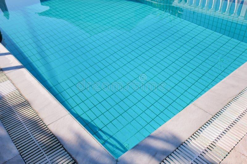 L'eau d?chir?e bleue dans la piscine dans la station de vacances tropicale avec le bord du trottoir Une partie de fond inf?rieur  photographie stock