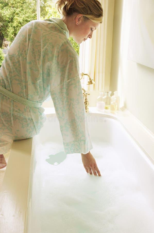 L'eau d'essai de femme dans la baignoire remplie de bulles images stock