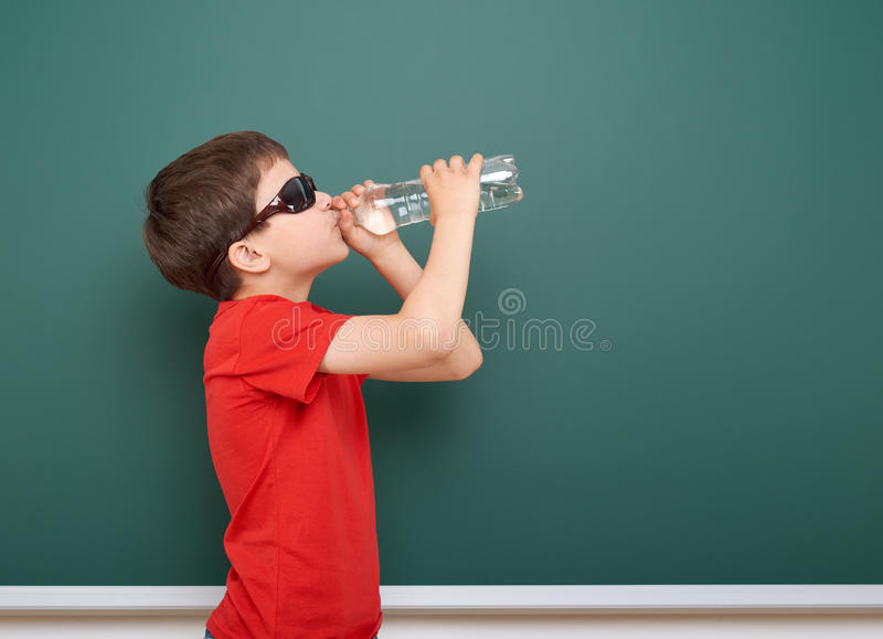 L'eau de boissons d'écolier de la bouteille près d'un tableau noir, l'espace vide, concept d'éducation photographie stock