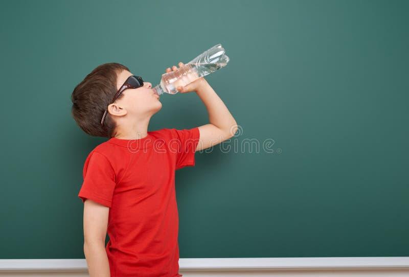 L'eau de boissons d'écolier de la bouteille près d'un tableau noir, l'espace vide, concept d'éducation images stock