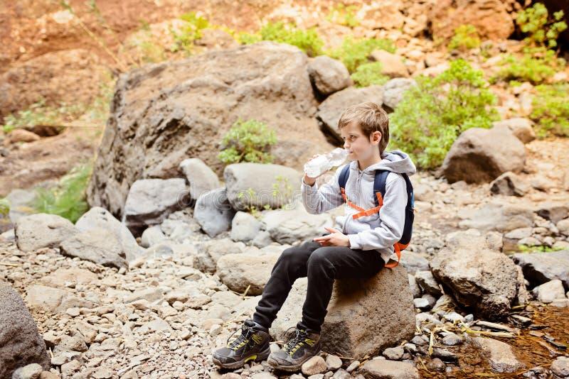 L'eau de bouteille potable d'enfant pendant le trekking en vallée de Masca photo stock