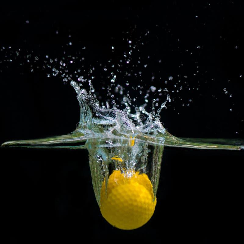 L'eau de chute de boule de golf image stock