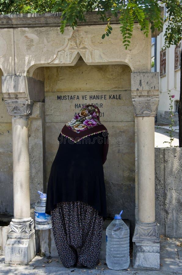 L'eau de cueillette de femme d'une fontaine dans Goreme, dans le Capp du sud photos stock
