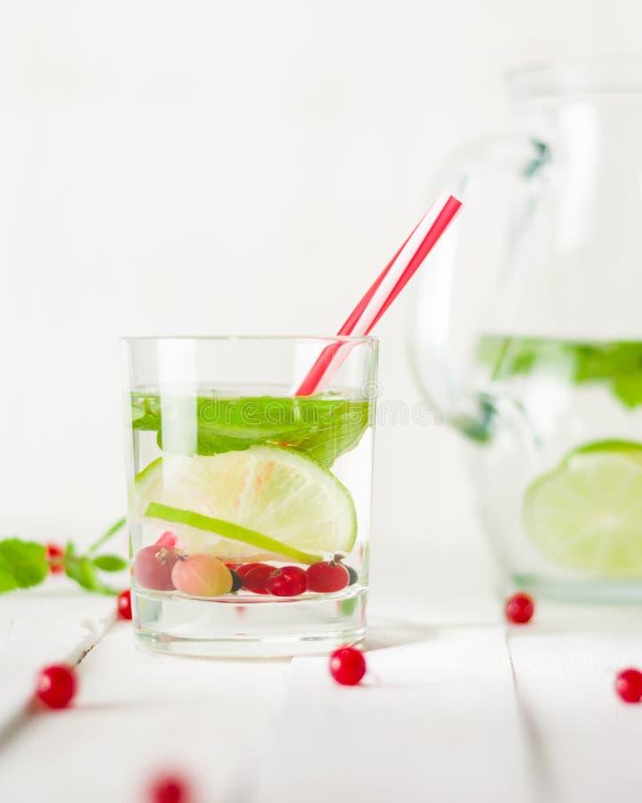 L'eau de Detox dans une cruche en verre et un verre Baies et chaux, rouge et vert Lames en bon état fraîches photo libre de droits