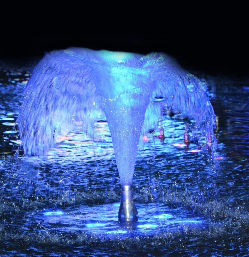 L'eau de fontaine éclairée à contre-jour la nuit photos stock