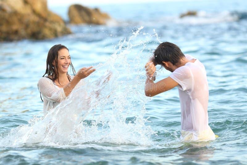 L'eau de lancement de plaisanterie de couples spontanés sur la plage photos stock