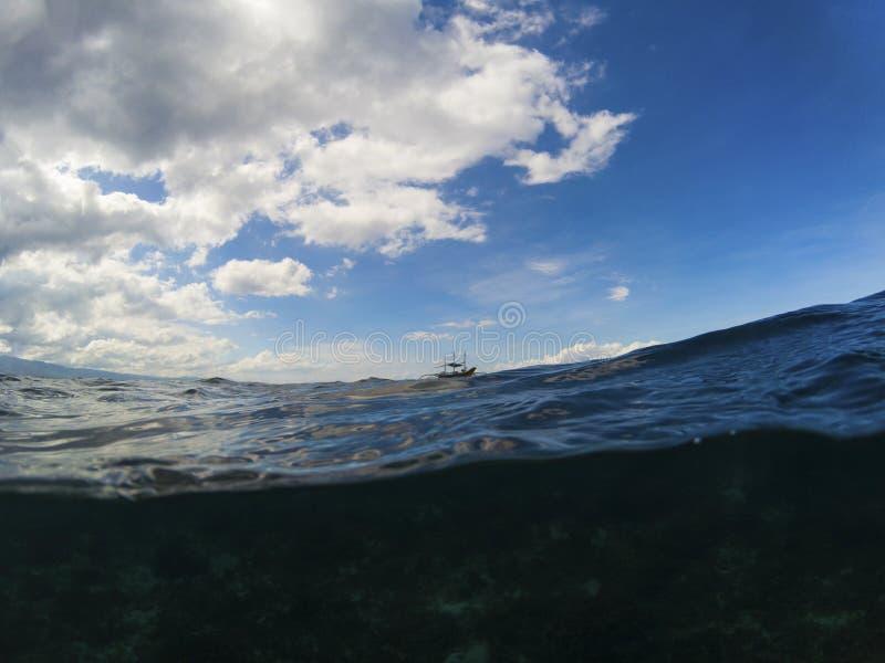 L'eau de mer foncée et le ciel bleu nuageux doublent la photo de paysage Bannière tropicale de bord de la mer image libre de droits