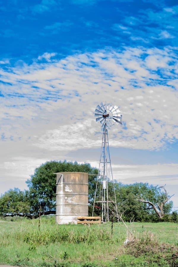 L'eau de pompage abandonnée de moulin à vent de Waterwell dans le réservoir d'eau grand à côté de la barrière le jour nuageux d'é image libre de droits