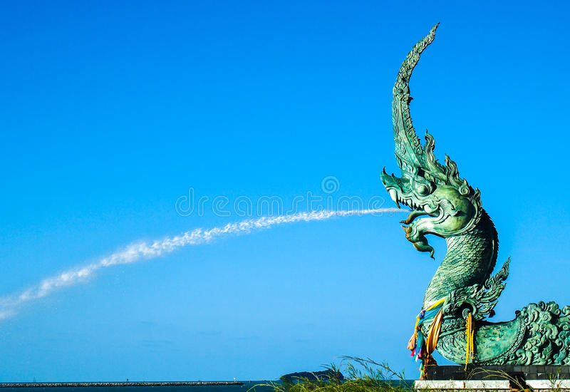 L'eau de pulvérisation de statue de Naga vers la mer avec le fond de ciel bleu photographie stock libre de droits